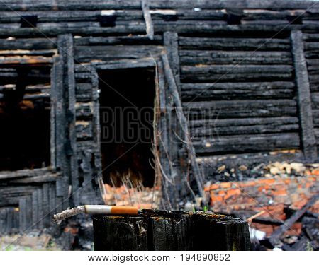 cigarette butt on the background of a burned wooden house, a fire with careless handling of a cigarette