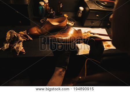 Cropped image of young concentrated man shoemaker at footwear workshop.