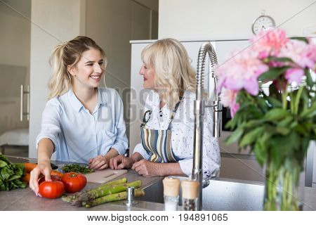 Smiling granddaughter and grandmother cooking healthy food at the kitchen at home