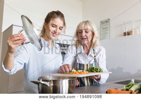 Smiling granddaughter helping her grandmother to put vegetables in a pot while cooking together at the kitchen