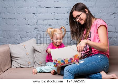 Young Mother And Two Year Old Girl With Blond Hair Sitting On The Couch And Using Laptop. Dressed In
