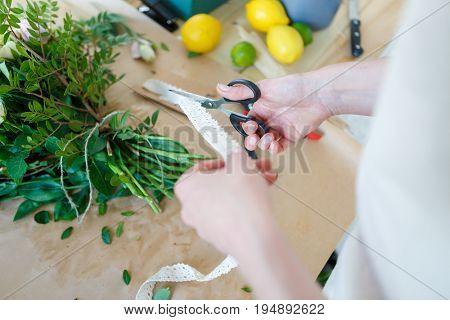 Florist cuts ribbon for bouquet