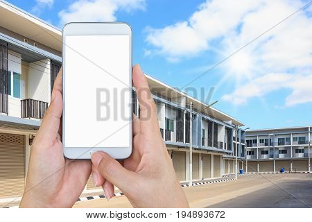 woman hand holding and touch screen smart phone looking for a new townhouses in suburb.