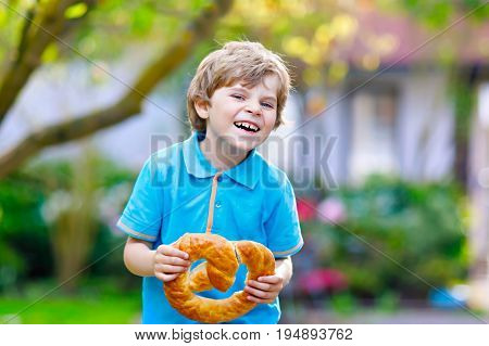 Adorable little kid boy eating huge big bavarian german pretzel. Happy blond child enjoying tasteful tratditional bread. Healthy food for happy kids.