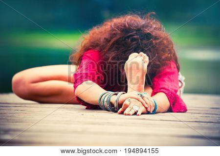 young woman practice yoga outdoor by the lake  focus on hands with lot of bracelets and rings healthy lifestyle concept