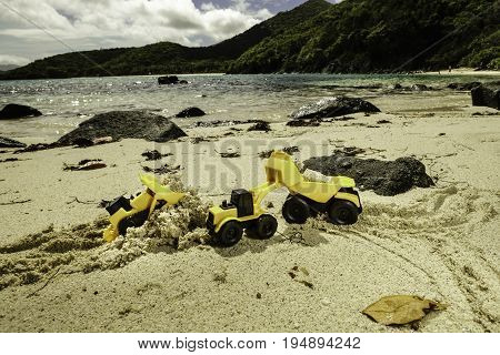 Toy construction trucks moving sand around on the beach of a tropical island, including a toy bulldozer, front loader, and dump truck