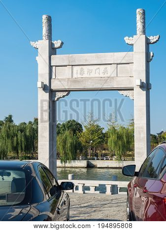 Suzhou, China - Nov 5, 2016: Stone gate in classical Chinese design named Wumen Impression (Chinese characters) on a public park, along the Waicheng River.