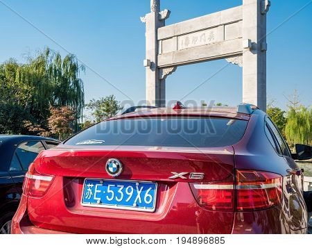 Suzhou, China - Nov 5, 2016: Late model BMW X6 parked in front of the stone gate in classical Chinese design named Wumen Impression (Chinese characters). In a public park, along the Waicheng River.