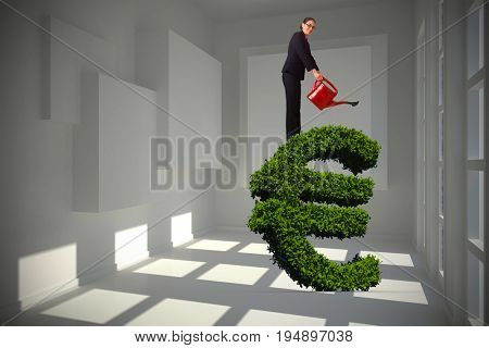 Businesswoman using red watering can against white room with squares at wall