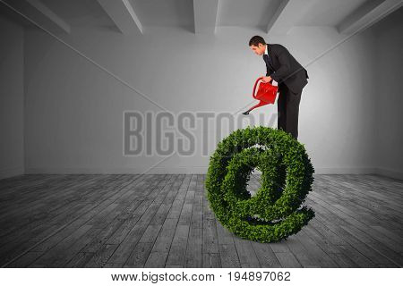 Businessman watering with red can against big room with white wall