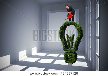 Businessman watering with red can against white room with square at wall