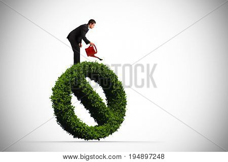 Businessman watering with red can against forbidden sign made of leaves