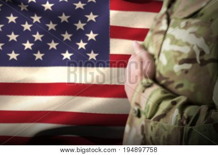 Mid section of military soldier taking oath against waving american flag