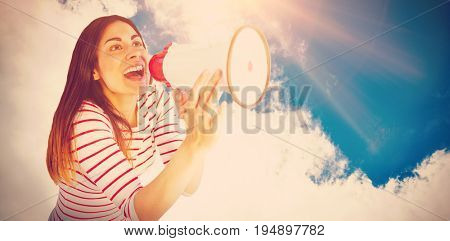 Young woman shouting with megaphone against low angle view of sky