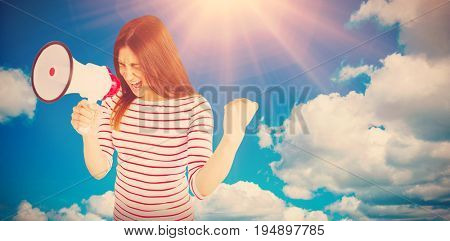 Excited young woman shouting with megaphone  against scenic view of blue sky