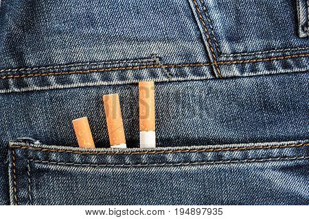 Three Cigarettes Are In The Back Pocket Of Blue Jeans
