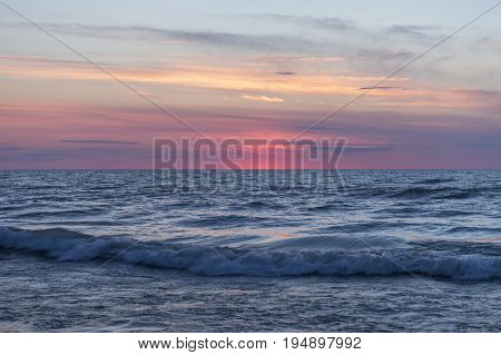 Waves Crashing And Rolling In Near Sea Shore Under A Pastel Sky After Sunset