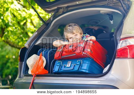 Adorable little kid boy sitting in car trunk just before leaving for summer vacation with his parents. Happy child with suitcases and toys going on journey. happy family traveling. Summer travel.