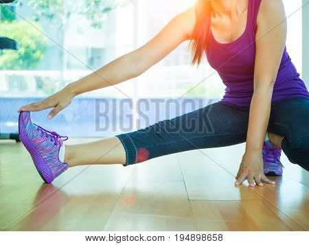 Fit woman stretching her leg to warm up in gym room with fitness equipments in backgroound