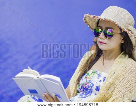 Woman in summer hat lying on deckchair and reading a book by the swimming pool. Vacation and relaxation summer travel concept.