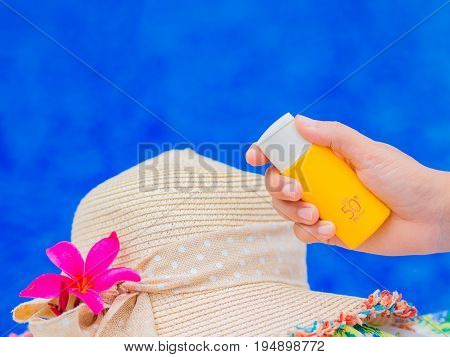Woman hand holding UV sunscreen bottle with summer hat and Red frangipani (plumeria) flowers by the swimming pool. Vacation and relaxation summer travel concept.