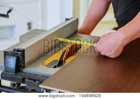 Carpenter using table saw cutting wood. handyman cutting plywood on circular saw in the new house