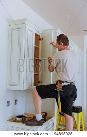 Installation of kitchen. Worker installs doors to kitchen cabinet. Installation of doors on kitchen cabinets