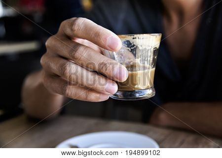 closeup of a young caucasian with a glass with caffe macchiato in his hand, sitting at a table in a coffeehouse