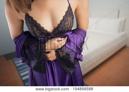 The woman in purple satin nightwear wake up for go to restroom.