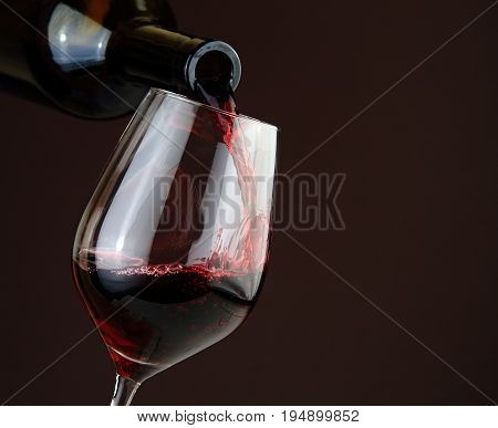 Wine and alcoholic theme. Pouring red wine on dark background. Wine pouring into a wine glass.