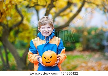 Happy cute little kid boy with halloween pumpkin lantern. Funny child in colorful clothes having fun and playing autumn garden or park on cold autumnal day.