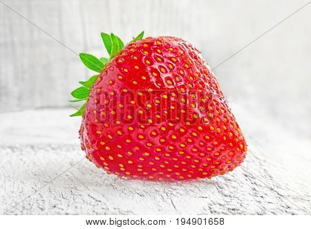 Fresh strawberries on white wooden table.