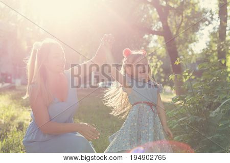 Family values. Mother holds daughter by the hand. Hand in hand. Family support. Same dresses and hairstyles. Backlight of the setting sun. Family look