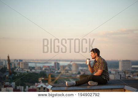 A man drinks coffee early in the morning on the roof. He looks into the distance and reflects. In the background the city landscape