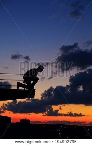Silhouette of a man against a background of clouds and golden sunset. He sits on the edge of the roof and looks down.