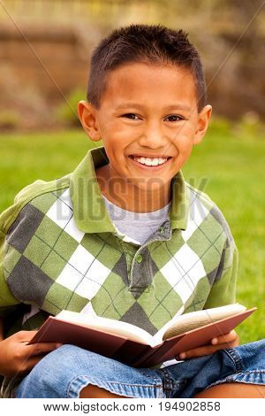 Happy young kids smiling and reading outside.