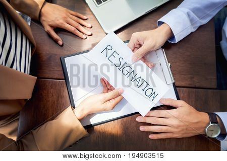 Hand Of A Businessman Hands Over A Resignation Letter On A Wooden Table To His Boss