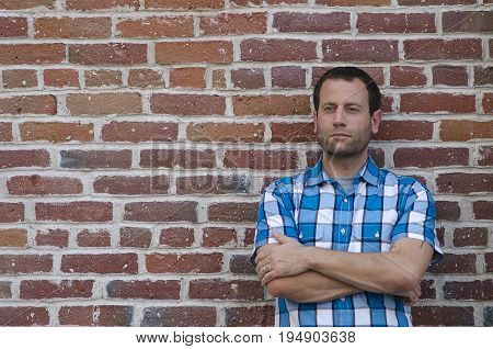 Portrait of an optimistic man leaning against a brick wall with his arms crossed thinking of what tomorrow will bring.