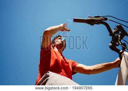 young man on a bicycle from below shot drinking water hot summer day real people concept