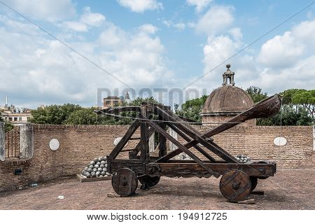 Rome Italy - August 19 2016: Old roman catapult in Castel Sant Angelo a cloudy summer day. The Mausoleum of Hadrian usually known as Castel Sant'Angelo is a towering cylindrical building in Rome