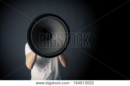 Young man holding a big speaker speaking loud concept on a dark studio background with space for text or image