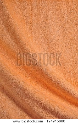 Soft orange color bath towel texture close up with small folds.