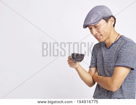 Asian Man Smiling At Cup Of Coffee Isolated On White