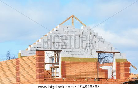 Attic construction with Mineral Wool Insulation House. Unfinished house with Building insulation. Attic Insulation with brick wall and wooden trusses and roof repair. Bricklaying Masonry Mansard Roof.