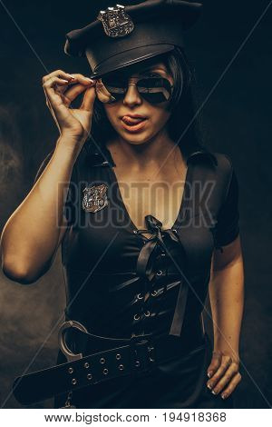 Pretty young woma in policeman costume over dark background