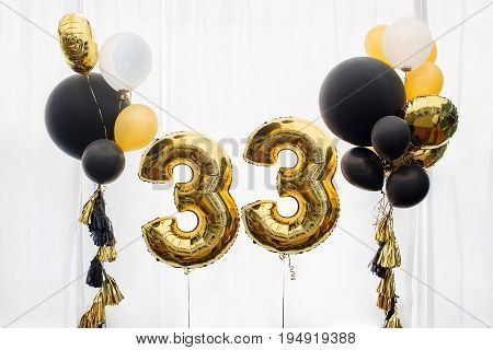 Decoration for birthday, anniversary, celebration of the thirty-third anniversary, white background, gold and black balloons with tassels