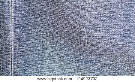 Denim jeans fabric texture background with seam for beauty, fashion and clothing concept design.