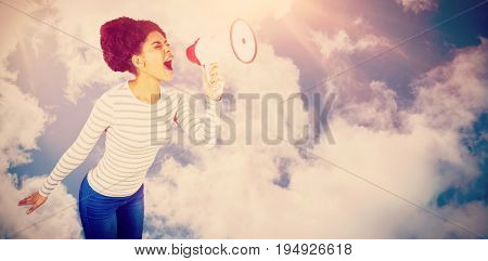 Carefree young woman yelling with megaphone  against bright blue sky with clouds