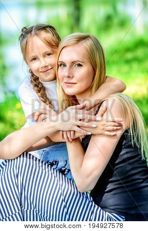 Family concept. Happy mother spending time with her little daughter in the park. Summer holidays.