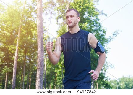 Wide shot of gorgeous boy running in park while listening to music